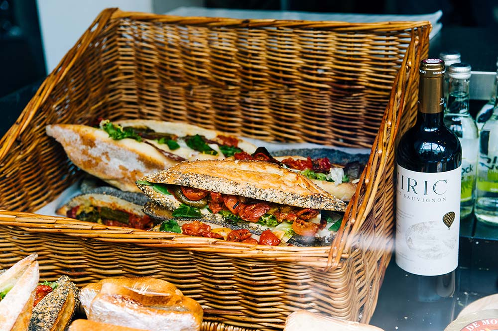 Picnic hamper with fresh baguette, cheese and tomatoes, Edible Bike Tours