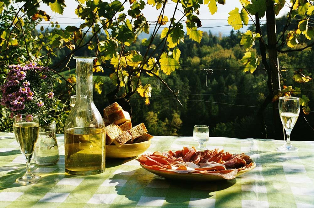 Picnic table with serrano ham, olive oil, white wine and fresh bread, on tour with Edible Bike Tours