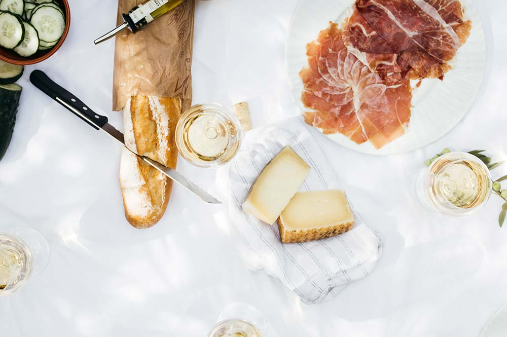 Platter of serrano ham, cheese, baguette, cucumber and olive oil, Edible Bike Tours